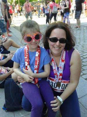 Woman and child wearing sunglasses and medals running
