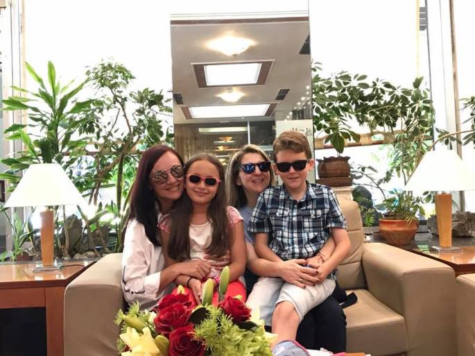 Two women on a couch with two children sitting on their knees, all wearing sunglasses