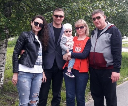 Four adults and a baby all wearing sunglasses in park