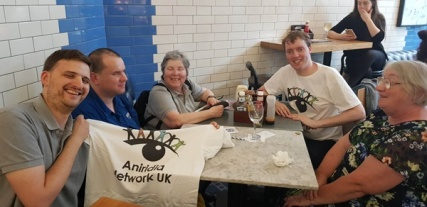 5 people around a table in London Victoria holding up a Aniridia Network UK t-shirt