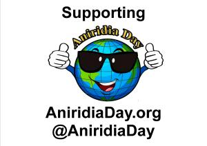 Poster showing the Aniridia Day logo - a cartoon image of the Earth, wearing sunglasses, smiling and giving 2 thumbs up. Above this are the words Supporting Aniridia Day. Below it is the website address AniridiaDay.org and the Twitter handle @AniridiaDay.