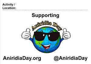 Poster showing the Aniridia Day logo - a cartoon image of the Earth, wearing sunglasses, smiling and giving 2 thumbs up. Above it is a space to enter an activity or location, followed by the words Supporting Aniridia Day. Below it is the website address AniridiaDay.org and the Twitter handle @AniridiaDay.