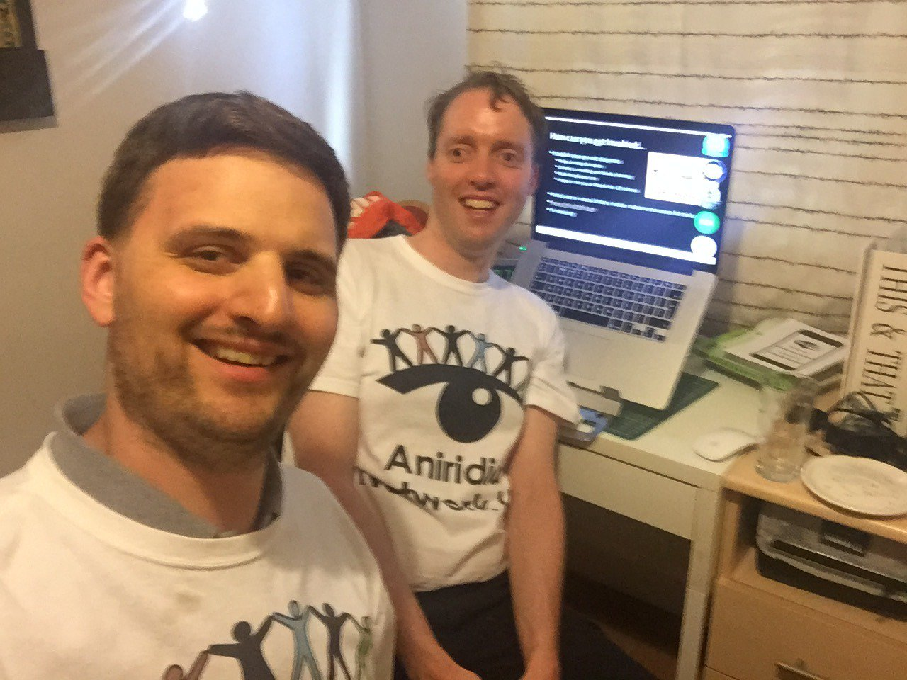 Two men wearing Aniridia Network UK t-shirts and a laptop showing a webinar in progress