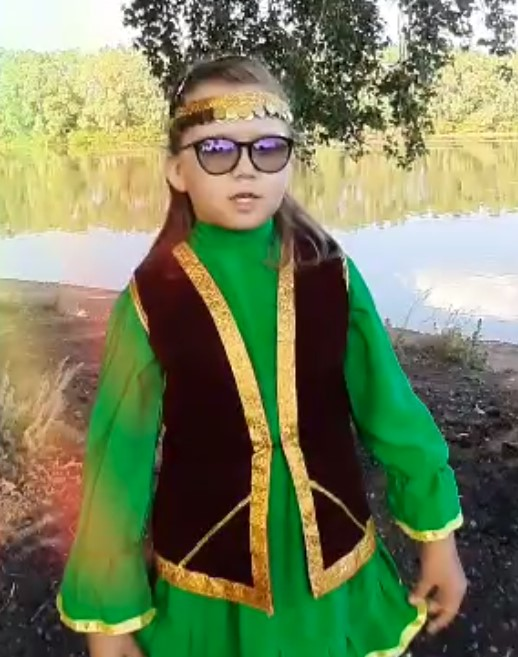 Andryushina wearing traditional green and black clothes of Bashkortostan