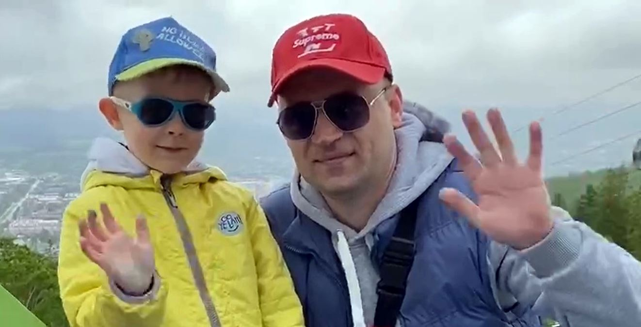 Man and boy both wearing sunglasses and cap waving at the camera